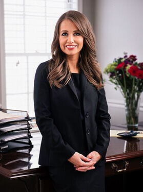 Smiling, Attorney Elizabeth M. Hennig stands in front of her desk, which has neat stacks of papers and a bouquet of flowers.