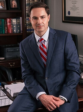 Attorney Evan L. Kaine sits on the edge of his desk in front of legal documents and books.