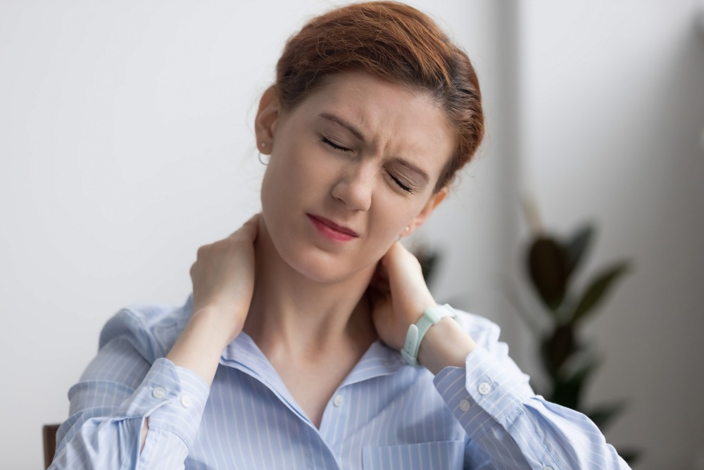 woman rubbing her neck in pain